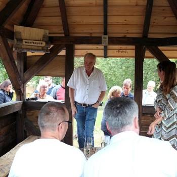 Die Einweihungsgäste nehmen in der Hütte platz